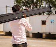 Uomo che porta un palo Fotografie Stock