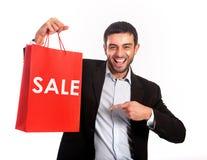 Uomo che porta un sacchetto della spesa rosso di vendita fotografia stock