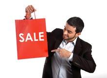 Uomo che porta un sacchetto della spesa rosso di vendita immagini stock libere da diritti