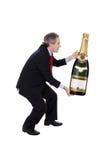 Uomo che porta una bottiglia surdimensionata del champagne fotografia stock