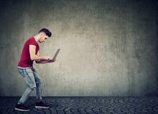 Uomo che pratica il surfing computer portatile moderno sulla parete grigia immagini stock