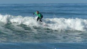 Uomo che pratica il surfing su Wave in California stock footage