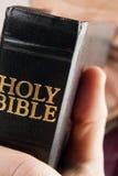 Uomo che prega tenendo la bibbia fotografia stock