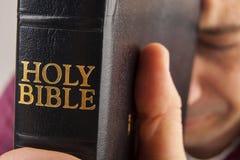 Uomo che prega tenendo la bibbia fotografia stock libera da diritti