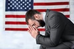 Uomo che prega sulla bandiera americana Fotografie Stock