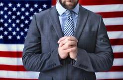 Uomo che prega sulla bandiera americana Fotografia Stock