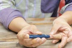 Uomo che preleva campione di sangue con la penna della lancetta all'interno Concetto del diabete immagine stock libera da diritti