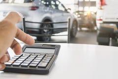 Uomo che preme calcolatore per finanza di affari sulla sala d'esposizione dell'automobile blu fotografie stock libere da diritti