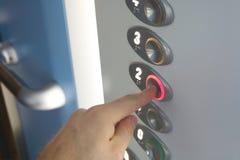 Uomo che preme il bottone del secondo piano nell'elevatore immagine stock libera da diritti