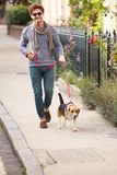 Uomo che prende cane per la passeggiata sulla via della città Fotografia Stock Libera da Diritti