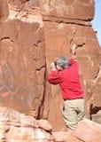 Uomo che prende fotografia del pannello del petroglifo immagini stock