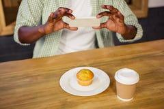 Uomo che prende immagine di un muffin fotografia stock