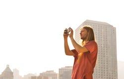 Uomo che prende immagine un giorno luminoso Fotografia Stock