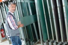 Uomo che prende la lastra di vetro da racking fotografie stock libere da diritti