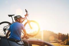 Uomo che prende la sua bicicletta dal tetto dell'automobile Concetto di ciclismo di montagna immagine stock libera da diritti