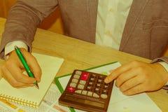 Uomo che prende le note, calcolatore sulla tavola Motivazione di successo, flussi finanziari, ricchezza immagini stock libere da diritti