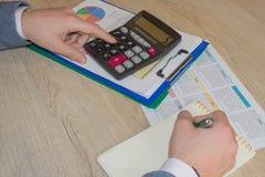 Uomo che prende le note, calcolatore sulla tavola Motivazione di successo, ricchezza di flussi finanziari fotografie stock