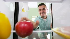 Uomo che prende mela dalla cucina del frigorifero a casa video d archivio