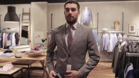 Uomo che prende selfie dallo smartphone al negozio di vestiti video d archivio