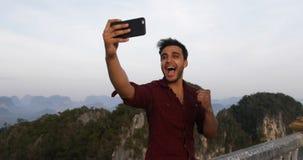 Uomo che prende Selfie sulla cima della montagna sullo Smart Phone delle cellule, latino-americano Guy Happy Smiling To Camera archivi video