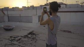 Uomo che prende un'immagine su un tetto archivi video