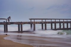 Uomo che prende una fotografia del pilastro della spiaggia nel giorno infuriante della pioggia immagini stock