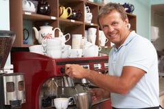 Uomo che produce caffè in caffè Immagini Stock