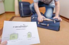 Uomo che prova a chiudere bagaglio a mano pieno Fotografia Stock Libera da Diritti