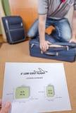 Uomo che prova a chiudere bagaglio a mano pieno Immagini Stock