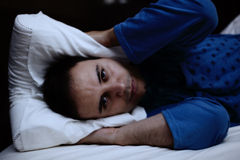 Uomo che prova a dormire nel suo letto Fotografia Stock Libera da Diritti