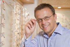 Uomo che prova sugli occhiali agli optometristi Immagine Stock