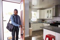 Uomo che proveniente a casa dalla porta di apertura e del lavoro dell'appartamento Fotografia Stock