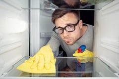Uomo che pulisce il frigorifero immagine stock libera da diritti