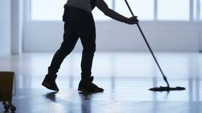 Uomo che pulisce il pavimento in una palestra di esercizio