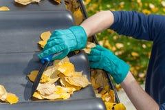 Uomo che pulisce il tetto in autunno Fotografia Stock