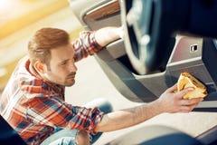 Uomo che pulisce l'interno della sua automobile Immagine Stock