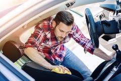 Uomo che pulisce l'interno della sua automobile Fotografia Stock