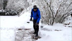 Uomo che pulisce neve profonda con la pala video d archivio