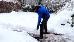 Uomo che pulisce neve profonda con la pala stock footage