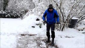 Uomo che pulisce neve profonda con la pala archivi video