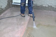 Uomo che pulisce un marciapiede con una rondella di pressione durante l'iarda della molla ed il lavoro del giardino fotografie stock