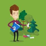 Uomo che raccoglie immondizia in foresta Immagini Stock Libere da Diritti