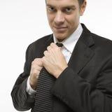 Uomo che raddrizza cravatta. Fotografia Stock