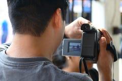 Uomo che registra famiglia su video Fotografia Stock