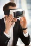 Uomo che regola i vetri di realtà virtuale sulla testa Fotografia Stock