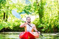 Uomo che rema con il kajak sul fiume Fotografie Stock