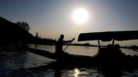 Uomo che rema una barca con un bello tramonto nei precedenti stock footage