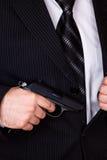 Uomo che ricava la sua pistola dalla casella del rivestimento Immagine Stock Libera da Diritti