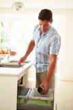 Uomo che ricicla lo spreco della cucina in recipiente Immagini Stock Libere da Diritti