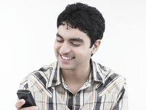 Uomo che ride del suo telefono delle cellule Immagine Stock